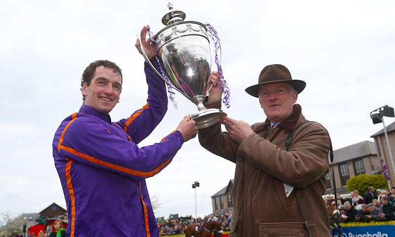Trainer Willie Mullins, right, and son jockey Patrick lift the cup in the parade ring after winning the Punchestown Champion Hurdle with Wicklow Brave on Friday.