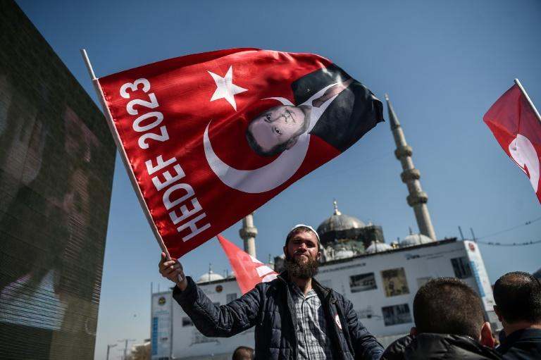 "A man waves a flag with a portrait of Turkish President Recep Tayyip Erdogan on April 11, 2017 during a ""yes"" campaign event in Istanbul's Eminonu district"