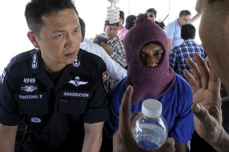 Police Major General Thatchai Pitaneelaboot (L) listens as a Rohingya trafficking victim leads a police unit to a camp where he was detained in Satun, southern Thailand in this March 27, 2014 file photo.    REUTERS/Andrew RC Marshall/Files