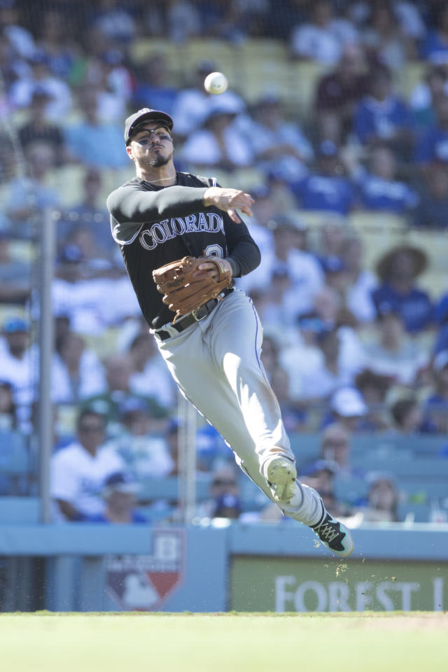 Colorado Rockies third baseman Nolan Arenado makes a throw to first base to get out Los Angeles Dodgers' Chris Taylor during the eighth inning of a baseball game in Los Angeles, Sunday, Sept. 22, 2019. (AP Photo/Sam Gangwer)