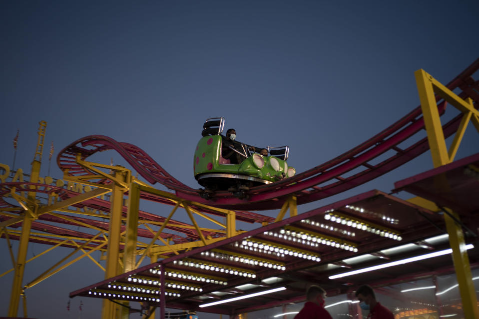 A man wears a mask on an amusement ride at the Mississippi State Fair, Wednesday, Oct. 7, 2020, in Jackson, Miss. At the fair, which is held every year in October and attracts people from across the racial spectrum, the vast majority of Black people are wearing masks. Most white people do not. (AP Photo/Wong Maye-E)