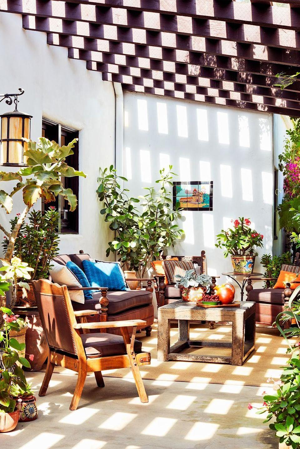 """<p>This outdoor area of a <a href=""""https://www.housebeautiful.com/design-inspiration/house-tours/a31136302/madeleine-stuart-los-angeles-home-tour/"""" rel=""""nofollow noopener"""" target=""""_blank"""" data-ylk=""""slk:SoCal home"""" class=""""link rapid-noclick-resp"""">SoCal home</a> by <a href=""""http://www.madelinestuart.com/"""" rel=""""nofollow noopener"""" target=""""_blank"""" data-ylk=""""slk:Madeline Stuart"""" class=""""link rapid-noclick-resp"""">Madeline Stuart</a> is filled with blooming plants like bougainvillea. Whether you add a few small potted plants, some large ones, or both, they'll easily enhance your work-from-outdoor setup. In this space, Stuart also included an area rug and seating with brown cushions to make it an extra-cozy garden oasis.</p>"""