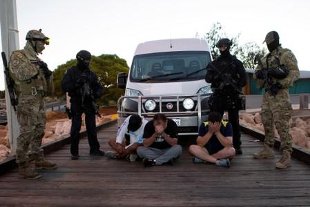 Police officers stand around suspects arrested during an operation that, according to police, resulted in the seizure of 1.2 tonnes of methamphetamine in Geraldton