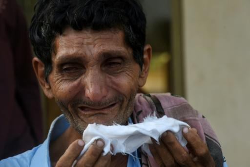 A private security guard's elder brother mourns his death during the funeral in Karachi -- the guard was one of four people killed by gunmen