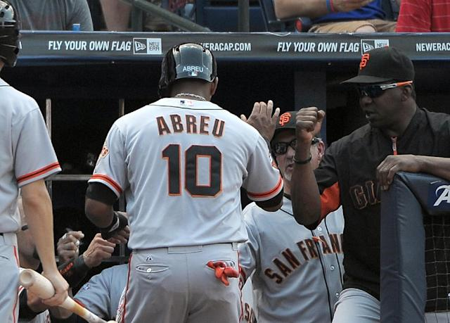 San Francisco Giants' Tony Abreu is congratulated by teammates after he scores against the Atlanta Braves during the third inning of their baseball game at Turner Field, Saturday, June 15, 2013, in Atlanta. (AP Photo/David Tulis)