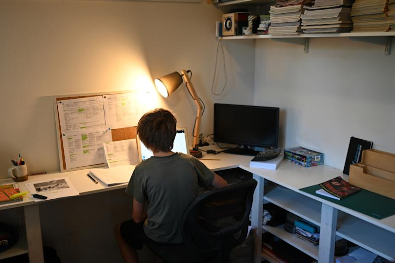 Pictured is a boy sitting at a desk doing his school work at home.