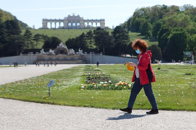 A woman wearing a protective face mask walks in the garden of Schoenbrunn Palace in Vienna as Austria prepares to ease lockdown restrictions. (Alex Halada/AFP via Getty Images)