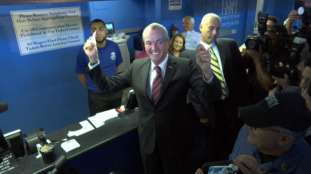 New Jersey Governor Phil Murphy holds two betting tickets, describing them as the first two legal sports bets in the history of this state at Monmouth Park Racetrack in Oceanport, New Jersey, Thursday, June 14, 2018. He placed $20 on Germany to win the World Cup soccer tournament, and $20 on the New Jersey Devils to win hockey's Stanley Cup next season. The wagers came a month after New Jersey won a U.S. Supreme Court case clearing the way for all 50 states to legalize sports betting if they choose. (AP Photo/Ted Shaffrey)