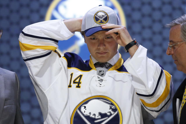 Sam Reinhart pulls on a Buffalo Sabres hat after being chosen second overall during the first round of the NHL hockey draft, Friday, June 27, 2014, in Philadelphia. (AP Photo/Matt Slocum)
