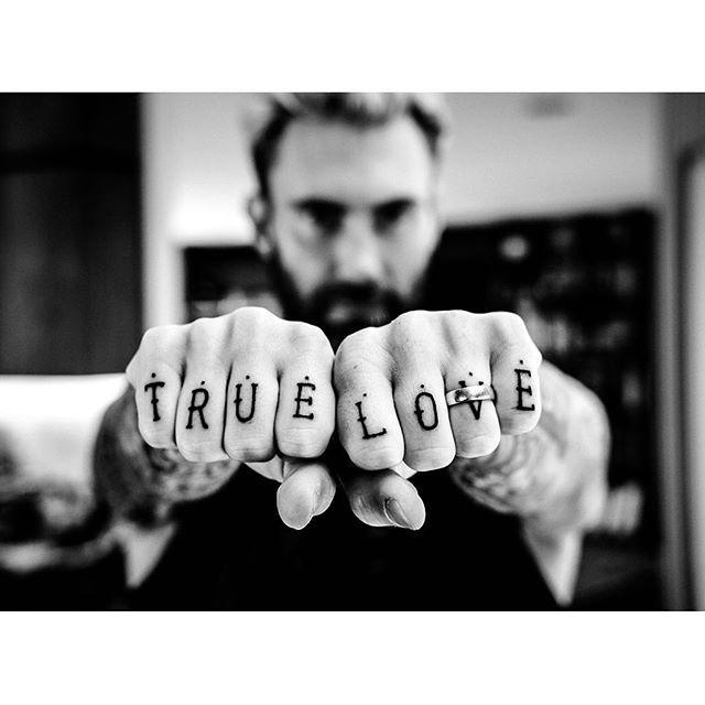 """<p>Of all of Adam Levine's many, <i>many </i>tattoos, perhaps the most touching are the ones on his knuckles, which he got in honor of wife Behati Prinsloo. After all, what says """"true love"""" quite like, well, inking the words """"true love"""" on your body forever?</p>"""