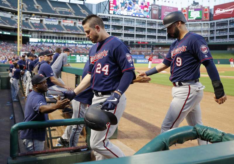 Minnesota Twins' C.J. Cron (24) and Marwin Gonzalez, right, are greeted at the dugout after Cron hit a two-run home run that scored Gonzalez during the first inning of the team's baseball game against the Texas Rangers in Arlington, Texas, Saturday, Aug. 17, 2019. The Twins won 12-7. (AP Photo/Tony Gutierrez)