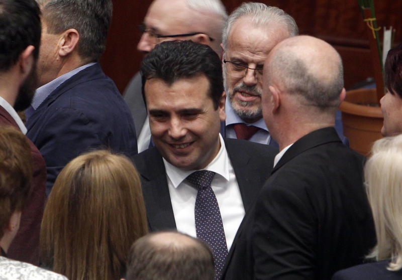 Macedonian Prime Minister Zoran Zaev, center, is greeted by lawmakers after the parliament voted in favor of the constitutional changes, in Macedonian Parliament in the capital Skopje, Friday, Jan. 11, 2019. Macedonia has fulfilled its part of a deal that will pave its way to NATO membership and normalize relations with neighboring Greece, after lawmakers approved constitutional changes that will rename the country North Macedonia. (AP Photo/Boris Grdanoski)