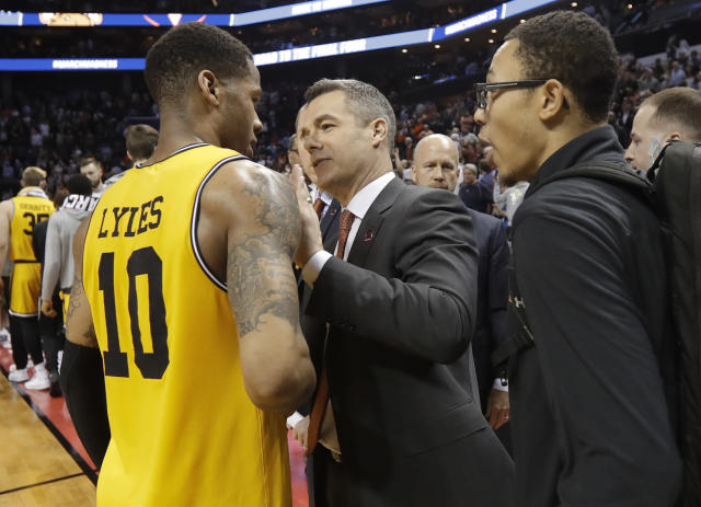 Virginia coach Tony Bennett (C) congratulates UMBC's Jairus Lyles (L) after a first-round game in the NCAA men's college basketball tournament in Charlotte, N.C., Friday, March 16, 2018. (AP Photo/Gerry Broome)