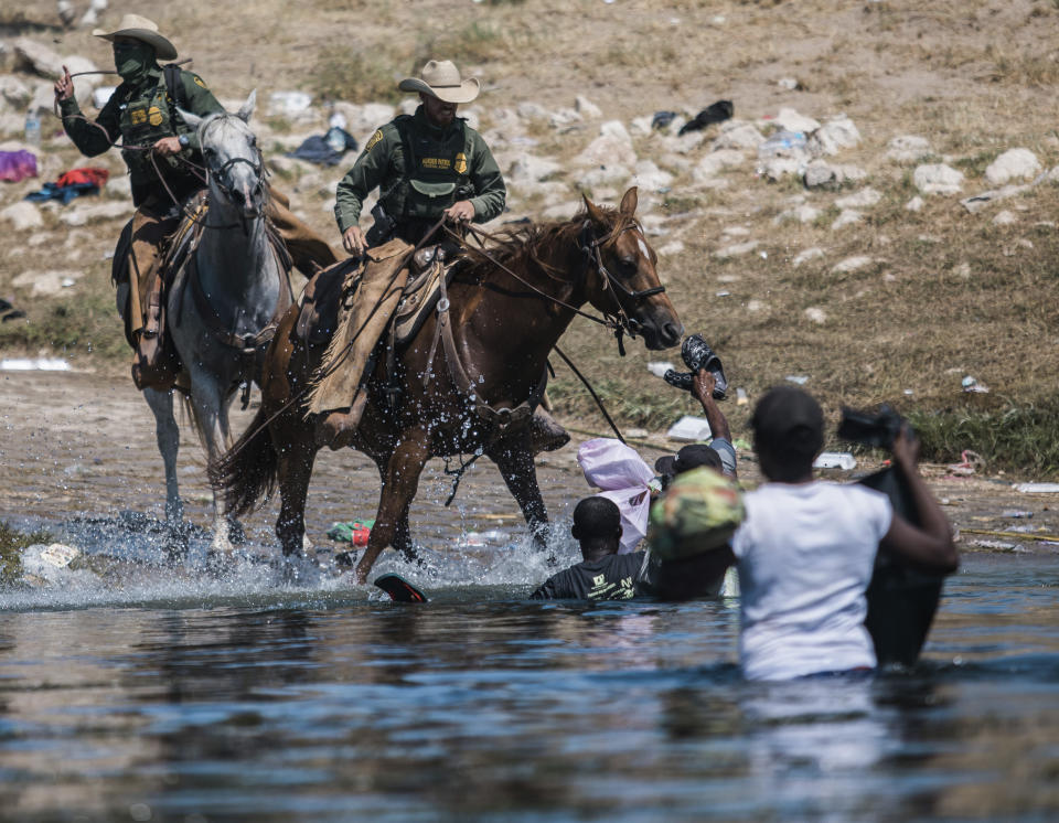 FILE - In this Sept. 19, 2021, file photo, U.S. Customs and Border Protection mounted officers attempt to contain migrants as they cross the Rio Grande from Ciudad Acuña, Mexico, into Del Rio, Texas. The Border Patrol's treatment of Haitian migrants, they say, is just the latest in a long history of discriminatory U.S. policies and of indignities faced by Black people, sparking new anger among Haitian Americans, Black immigrant advocates and civil rights leaders.( AP Photo/Felix Marquez, File)