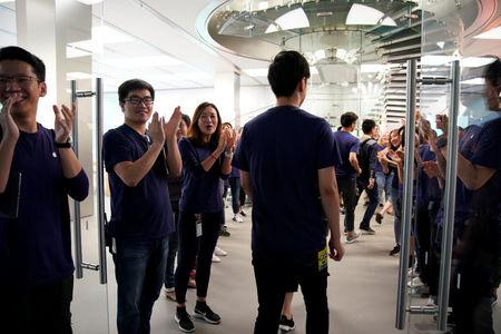 Staff members applaud customers as they arrive to purchase Apple's new iPhone 8 after it goes on sale at an Apple Store in Shanghai