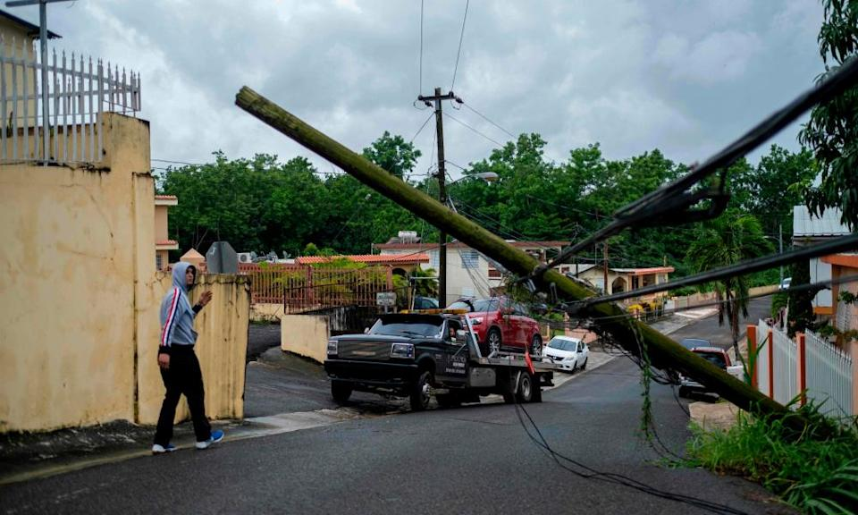 A man guides a tow truck under a downed power line pole after Tropical Storm Isaias affected the area in Mayaguez, Puerto Rico last week.