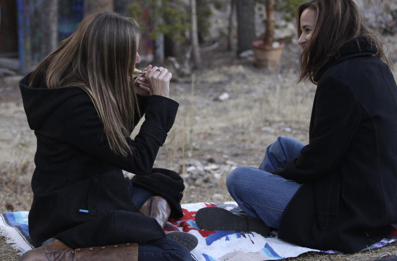 In this Nov. 19, 2012 photo, two women smoke marijuana together, behind a home in the woods near the small Rocky Mountain town of Nederland, Colo. On Nov. 6, 2012, Colorado and Washington state legalized the recreational use of marijuana. The two states, both culturally and politically, offered fertile ground for legalization advocates - Washington for its liberal politics, Colorado for its libertarian streak, and both for their Western independence. (AP Photo/Brennan Linsley)