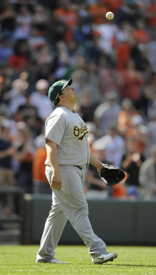 FILE - In this April 29, 2012, file photo, Oakland Athletics pitcher Bartolo Colon tosses the ball in the air after committing a throwing error during the ninth inning of a baseball game against the Baltimore Orioles in Baltimore. Colon, a former AL Cy Young Award winner, has been suspended for 50 games by Major League Baseball on Wednesday, Aug. 22, 2012, after testing positive for testosterone. (AP Photo/Gail Burton, File)