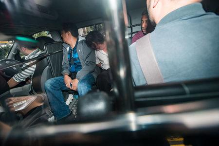 Suspects, part of a group of 17 detained over their part in an alleged oil theft at Shell's Pulau Bukom refinery, arrive in a van at the State Courts, Singapore January 13, 2018. REUTERS/Calvin Wong