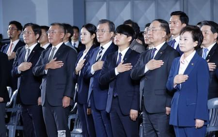 South Korean President Moon Jae-in delivers and Chief Vice Chairman of Hyundai Motor Group Chung Eui-sun salute to the national flag during a ceremony declaring country's vision to lead future mobility tech at Hyundai Motor's Namyang R&D Center in Hwaseong
