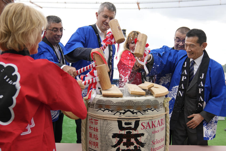 Japanese ambassador to Romania Hiroshi Ueda, right, along with Romanian officials breaks the cover of a sake barrel during a ceremony on the river Danube at the construction site of a suspension bridge across the Danube river, in Braila, Romania, Thursday, Aug. 26, 2021. The bridge, built by Japanese and Italian companies, with a span of 1,974.3 meters, will be the largest of its kind in Romania and the third in the European union. The event also marked 100 years of diplomatic relations between Japan and Romania. (AP Photo/Vadim Ghirda)