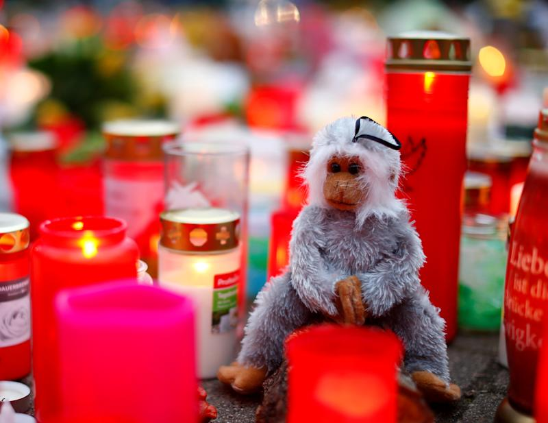 A toy monkey is seen between flowers and candles outside the zoo of Krefeld after a monkey house burned down and dozens of animals were killed by the fire in Krefeld, Germany, January 2, 2020. REUTERS/Thilo Schmuelgen TPX IMAGES OF THE DAY