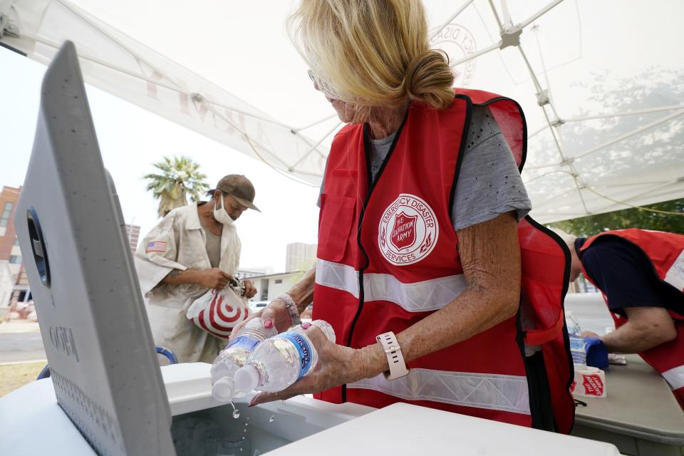 Salvation Army hydration station volunteer Kathleen McAllister, right, hands out water during a heatwave sending temperatures above 115-degrees, Tuesday, June 15, 2021, in Phoenix. (AP Photo/Ross D. Franklin)