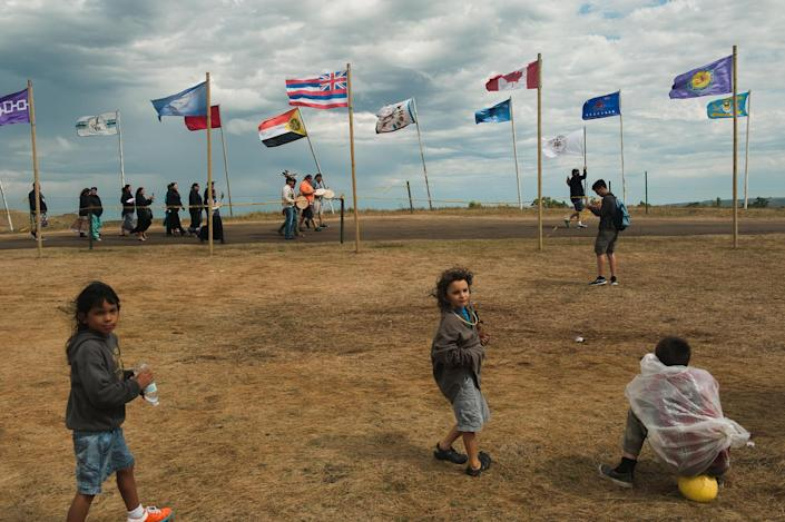<p>Children watch members of the Saginaw Chippewa Reservation of Mount Pleasant, Mich., enter an encampment of protestors opposing the Dakota Access oil pipeline near the Standing Rock Sioux reservation in Cannon Ball, N.D., on Sept. 7, 2016. (Photo: Andrew Cullen/Reuters) </p>