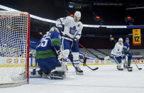 Vancouver Canucks goalie Thatcher Demko, left, makes the save while being screened by Toronto Maple Leafs' Auston Matthews (34) during the second period of an NHL hockey game in Vancouver, British Columbia, on Saturday, March 6, 2021. (Darryl Dyck/The Canadian Press via AP)