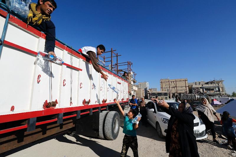 Members of the Iranian civil defence hand out bottles of water to earthquake survivors in the town of Sar-e Pol-e Zahab in Iran's western Kermanshah province on November 14, 2017 (AFP Photo/ATTA KENARE)