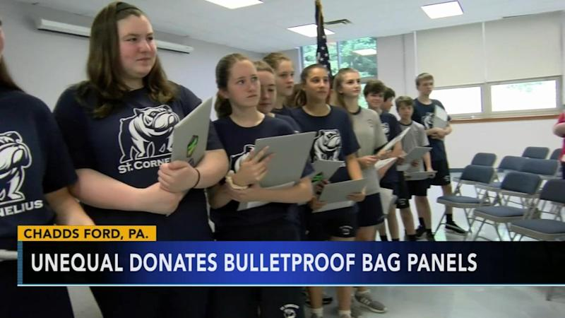 Middle school graduates receive a bulletproof shield that their principal hopes they will carry in high school. More