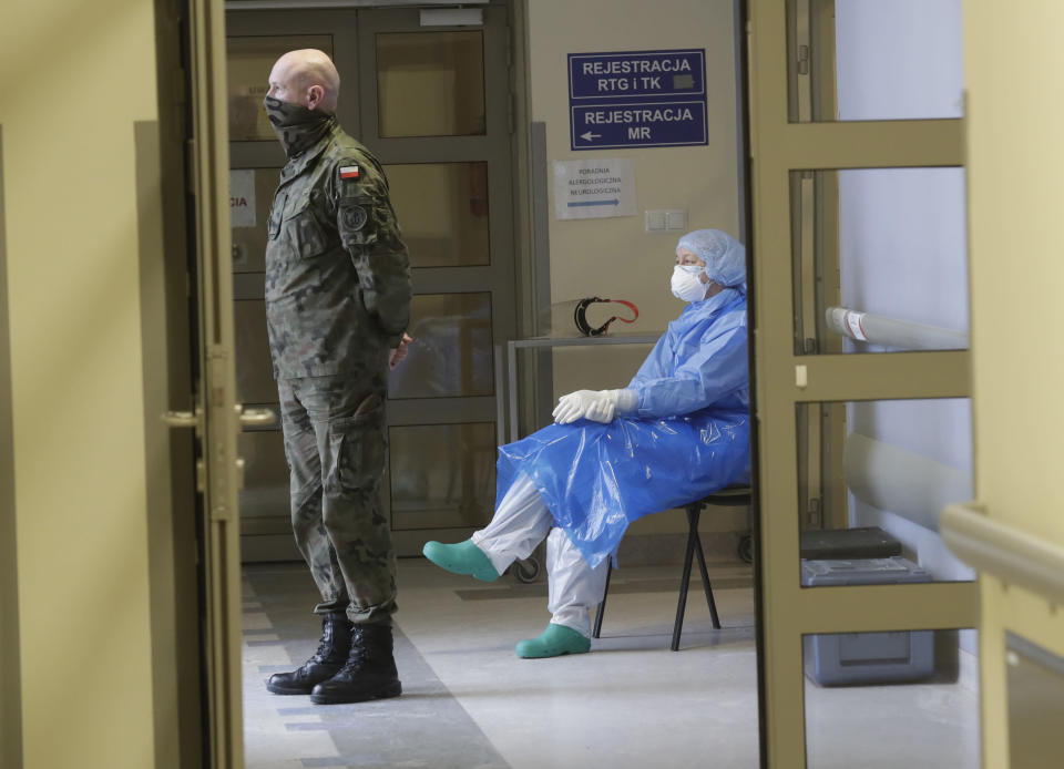 A Polish soldier and a nurse wait in a hallway in a hospital in Krakow, Poland, Friday Feb. 12, 2021, during the vaccination of teachers against the coronavirus with the AstraZeneca vaccine. As Poland began vaccinating teachers on Friday, many say they are unhappy that they are getting AstraZeneca vaccines against the coronavirus, rather than the Pfizer shots earmarked for health care workers and the elderly. Nearly a year into the pandemic, many Europeans and others globally are desperate to get vaccinated and return to normal life. But many don't want just any vaccine. (AP Photo/Czarek Sokolowski)