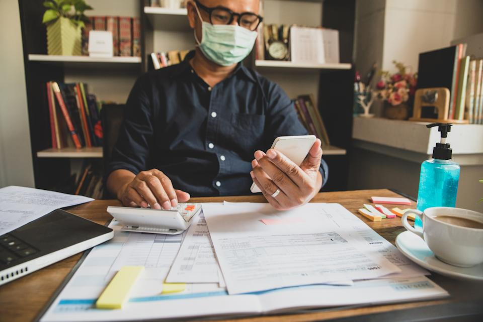 Budget planning concept,Accountant wear mask is calculating company's annual tax.Calendar 2019 and personal income tax forms for those who have income under US law placed on home desk.
