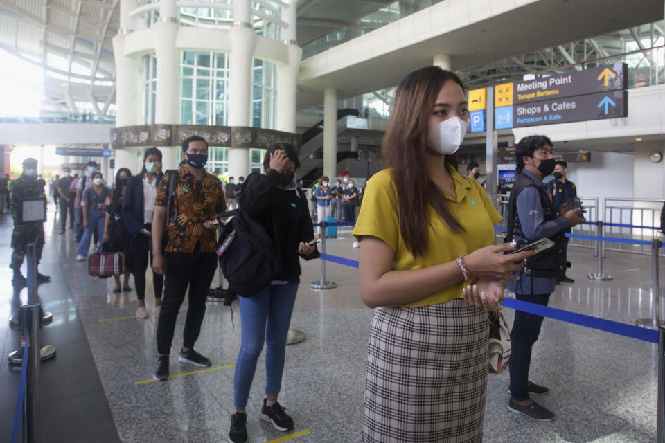 Mock passengers queue as they arrival at Ngurah Rai International Airport during its reopening drills in Bali, Indonesia on Saturday, Oct. 9, 2021. Indonesia plans to reopen the airport in the resort island of Bali for international flights on Oct. 14, after closing it for more than a year because of the COVID-19 pandemic. (AP Photo/Firdia Lisnawati)