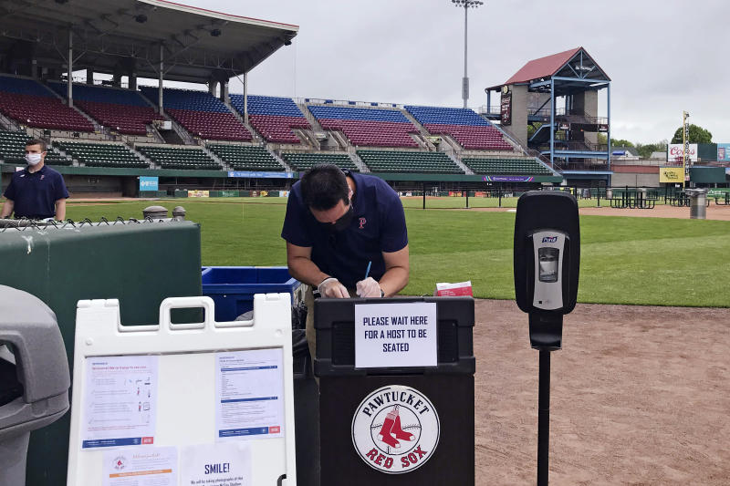 """A worker prepares for guests to dine on the field at McCoy Stadium, home of the Pawtucket Red Sox, in Pawtucket, Rhode Island, Wednesday, May 27, 2020. With the minor league baseball season on hold due to the coronavirus pandemic, the Triple-A affiliate of the Boston Red Sox had found another use for its home field. Starting next weekend, """"Dining on the Diamond"""" will allow PawSox fans and others just longing for a taste of baseball to sample typical ballpark fare on the McCoy Stadium infield.(AP Photo/Jimmy Golen)"""