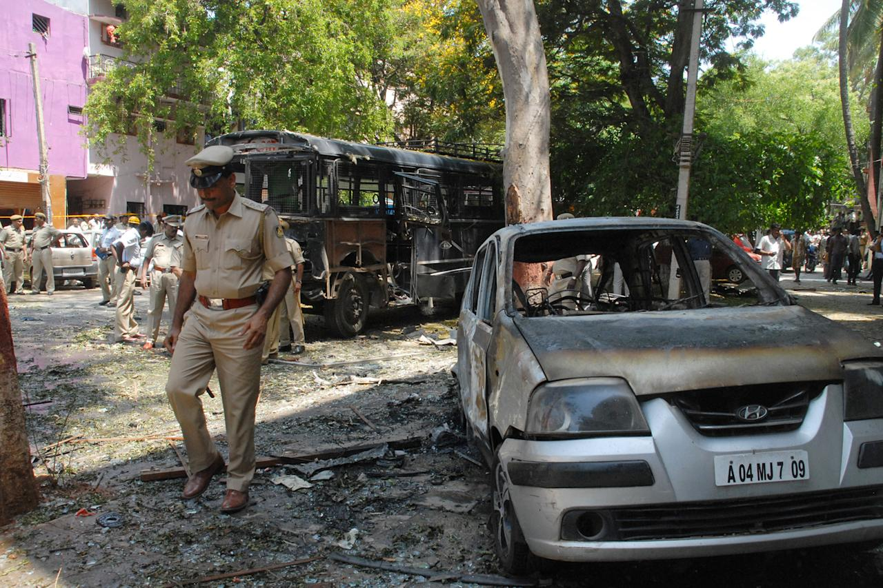 An Indian policeman walks past charred vehicles following a blast near the Bharatiya Janata Party (BJP) office in Bangalore on April 17, 2013. Police in the southern city of Bangalore said Wednesday they were investigating a minor blast outside the office of a political party which injured 12 people.