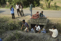 FILE - In this May 14,2017, file photo, Indian civilians take temporary shelter beneath a culvert as they wait for transport to move to safer places after mortar shells were fired allegedly from the Pakistan side of the border, at a residential area near Line of Control on the India Pakistan border at Jhanghar village, in Nowshera, India. The Line of Control, a highly militarized de facto border that divides the disputed region between the two nuclear-armed rivals India and Pakistan, and a site of hundreds of deaths, is unusually quiet after the two South Asian neighbors agreed in February, 2021, to reaffirm their 2003 cease-fire accord. (AP Photo/Channi Anand, File)