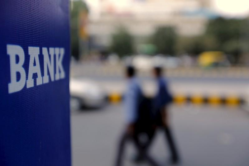 FILE PHOTO: Commuters walk past a bank sign along a road in New Delhi