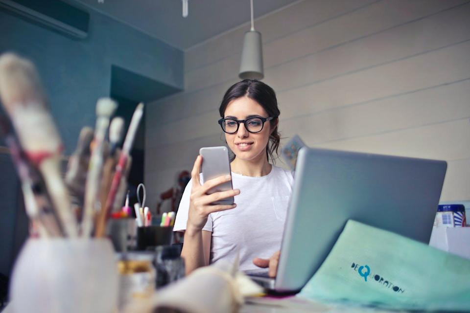 Woman sitting at laptop, wearing glasses looks at cellphone