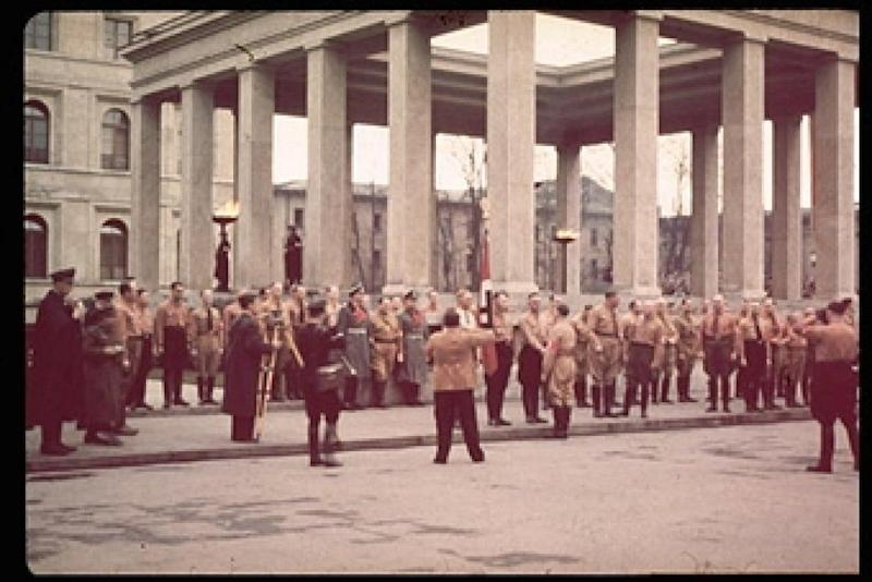 During a ceremony in remembrance of 1923 Beer Hall Putsch, German Fuhrer and Reichskanzler Adolf Hitler (1889 - 1945) (center, back to camera) shakes hands with a uniformed Nazi party member as others stand at attention in front of one of the two Ehrentempeln (or Honor Temples), designed by architect Paul Troost, in Koenigplatz, Munich, Germany, November 9, 1937. Also visble are German Reich Marshal Hermann Goering (1893 - 1946) (between the two men in grey overcoats) and Rudolf Hess (1894 - 1987). The temples, and the ceremony, were to honor the sixteen men who died for their participation in the Putsch, Hitler's failed 1923 coup attempt. Other visible buildings are, at left, the Verwaltungsbau (or Nazi Party Administration building, also designed by Troost) and, at right, the Staatsgalerie, an art museum. (Photo by Hugo Jaeger/Timepix/Time Life Pictures/Getty Images)
