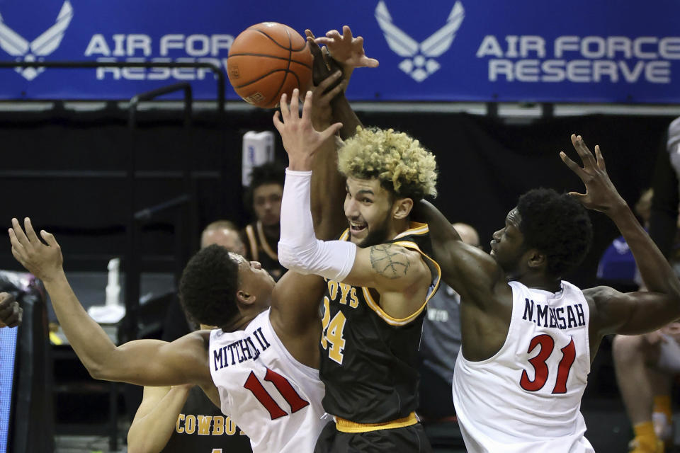 Wyoming guard Hunter Maldonado (24) reaches for a rebound with San Diego State forward Matt Mitchell (11) and forward Nathan Mensah (31) during the first half of an NCAA college basketball game in the quarterfinal round of the Mountain West Conference tournament Thursday, March 11, 2021, in Las Vegas. (AP Photo/Isaac Brekken)
