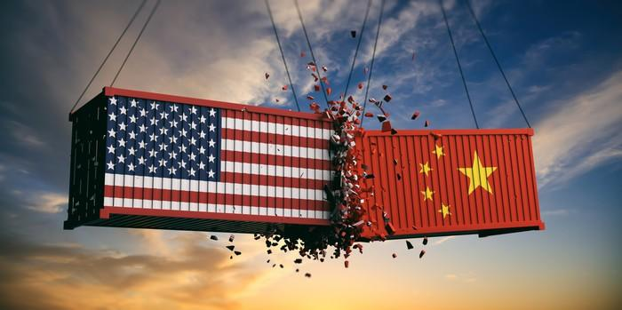 Two suspended cargo containers crashing together, one with a U.S. flag and one with a Chinese flag.