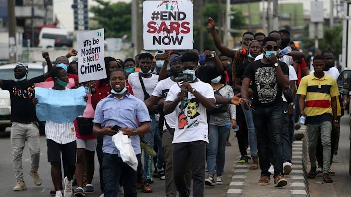 Protesters hold banners as they walk along a road during a protest against the Nigeria rogue police, otherwise know as Special Anti-Robbery Squad (SARS), in Ikeja district of Lagos, Nigeria, 09 October 2020.