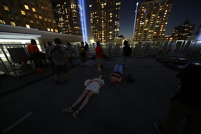 <p>Visitors lie on the ground to view the Tribute in Light on Sept. 5, 2018. (Photo: Gordon Donovan/Yahoo News) </p>