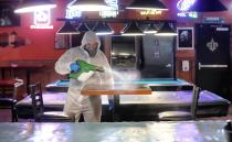 FILE - In this May 22, 2020, file photo, Tyler Page, a technician with 6 & Fix, Inc., help disinfect and protect Sharky's Place in Raleigh, N.C. Coronavirus cases are rising in nearly half the U.S. states, as states are rolling back lockdowns. (Robert Willett/The News & Observer via AP)