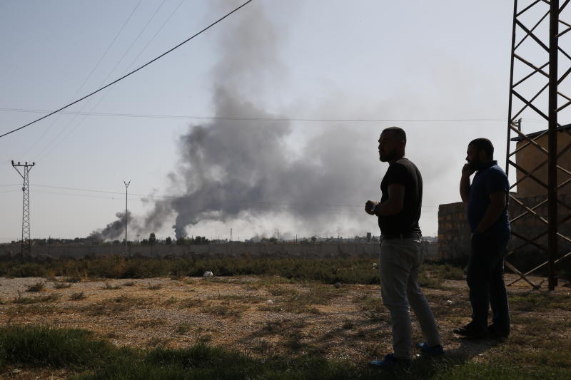 In this photo taken from the Turkish side of the border between Turkey and Syria, in Akcakale, Sanliurfa province, southeastern Turkey, people watch as smoke billows from targets inside Syria during bombardment by Turkish forces, Oct. 10, 2019. (Photo: Lefteris Pitarakis/AP)