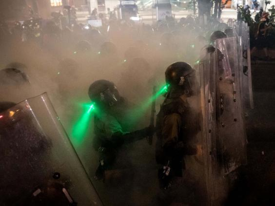 Police move forward through tear gas as they clash with protesters (Chris McGrath/Getty Images)