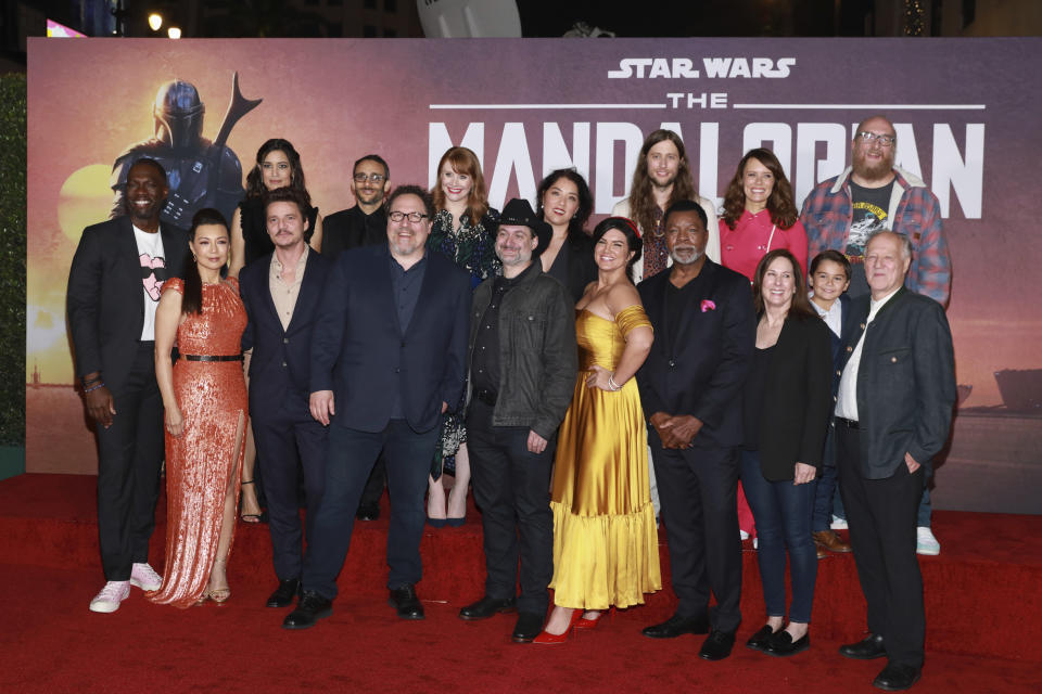 """Rick Famuyiwa, from left, Ming-Na Wen, Julia Jones, Pedro Pascal, Omid Abtahi, Jon Favreau, Bryce Dallas Howard, Dave Filoni, Deborah Chow, Gina Carano, Ludwig Goransson, Carl Wethers,Emily Swallow, Kathleen Kennedy, Aidan Bertola, Brian Posehn, and Werner Herzog attend the LA Premiere of """"The Mandalorian"""" at the El Capitan theatre on Wednesday November 13, 2019 in Los Angeles. (Photo by Mark Von Holden/Invision/AP)"""