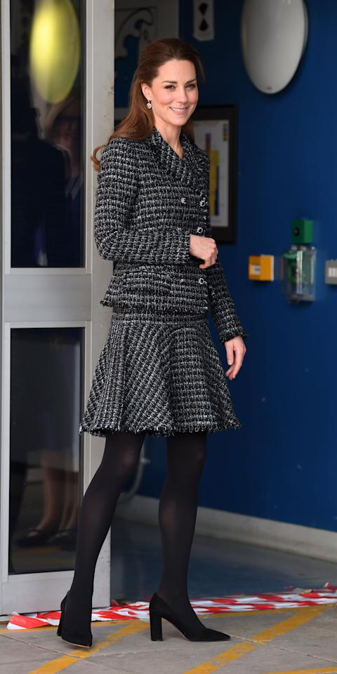 "<p>While visiting a children's hospital, Kate Middleton wore a <a href=""https://click.linksynergy.com/deeplink?id=93xLBvPhAeE&mid=37508&murl=https%3A%2F%2Fwww.farfetch.com%2Fshopping%2Fwomen%2Fdolce-gabbana%2Fitems.aspx&u1=IS%2CKateMiddleton%2Canesta%2C%2CIMA%2C3517646%2C202001%2CI"" target=""_blank"">Dolce & Gabbana</a> tweed set with black stockings, and pointed-toe heels.</p>"
