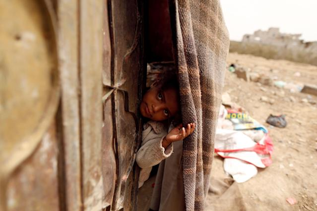 <p>A girl displaced from the Red Sea port city of Hodeidah looks from behind a door of her family shelter in Sanaa, Yemen July 18, 2018. (Photo: Khaled Abdullah/Reuters) </p>